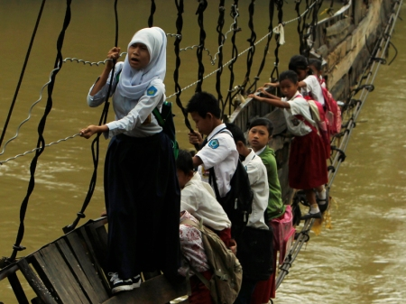 Students hold on to the side steel bars of a collapsed bridge as they cross a river to get to school at Sanghiang Tanjung village in Lebak regency